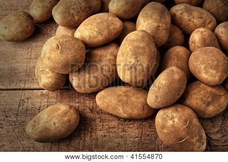 Fresh potatoes on rustic wooden background
