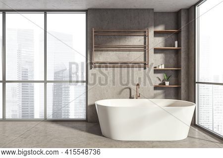 Bathing Interior With White Bathtub On Grey Floor And Heated Towel Rail. Panoramic Window With City