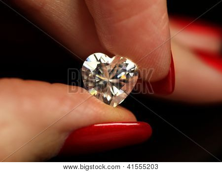 Fingers holding heart shape diamond