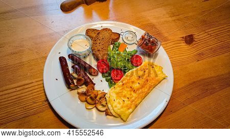 A Delicious And Delicious Breakfast Of Fried Eggs, Sausages, Champignons As Well As Lettuce And Toma