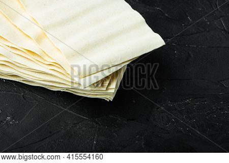 Dried Uncooked Lasagna Pasta Sheets Set, On Black Stone Background, With Copy Space For Text