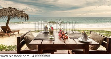 Romantic Dinner In Beach Restaurant Or Cafe, Sri Lanka. Table With Cocktail And Flowers On Ocean Bac
