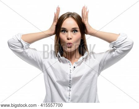 A Surprised Young Woman Holds Her Head In Her Hands. A Beautiful Girl Looks Shocked With A Surprised