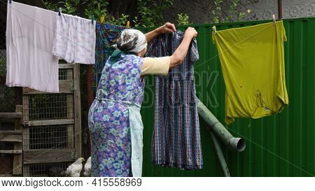 80s Great-grandmother In Traditional Clothes Hanging Colorful Washed Wet Laundry With Clothespins On