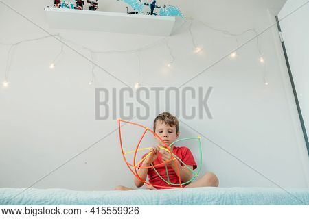 Boy Playing With Straws Constructor On The Bed In His Room.