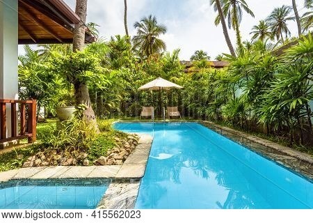 Sri Lanka - Nov 4, 2017: Pool With Umbrella And Beach Beds At Tropical Hotel Or Vacation Home. Beaut