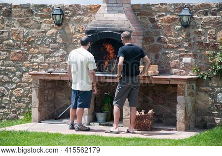 Two Man Dressed With Informal Clothes Preparing A Meat Barbecue At The Backyard. Big Oven And Counte