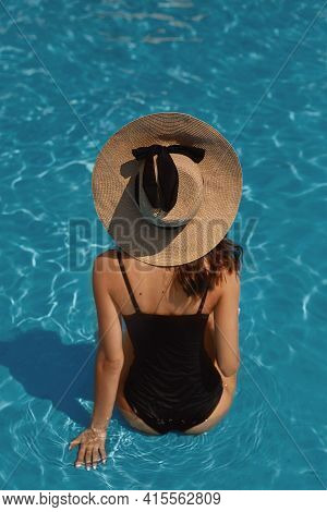 A Young Gorgeous Woman With Sexy Big Breasts And Slim Waist In A Black Swimsuit Posing In The Swimmi