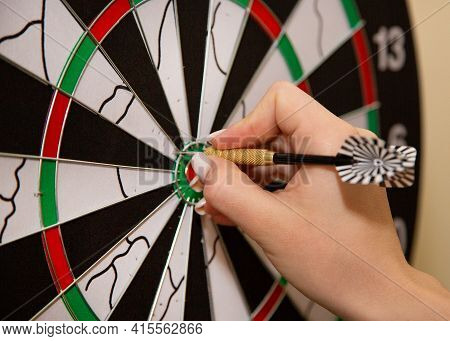 The Girl Plays Darts. Dart Darts In The Hands Of A Girl. Target And Dart Darts Game.