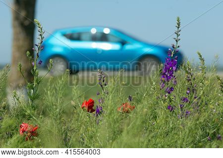Bright Blue Car And Spring Flowers On The Foreground. Road Trip Concept. Spring, May, Cremea