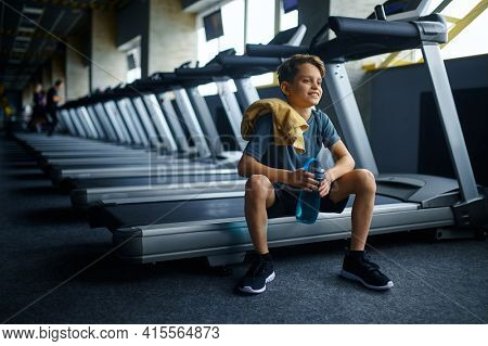 Youngster with water sitting on treadmill in gym