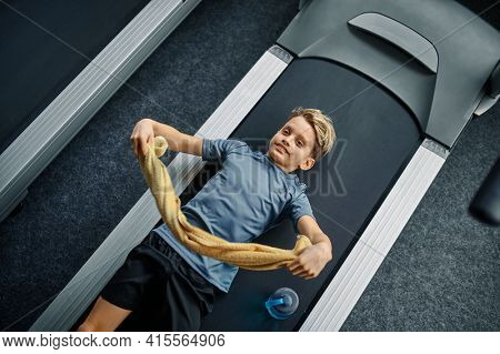 Tired youngster lying on treadmill in gym