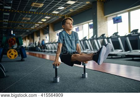 Youngster doing exercise with dumbbells in gym