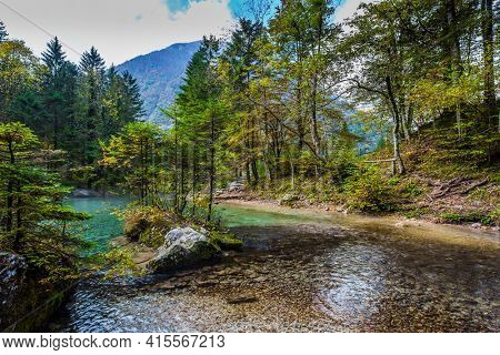 Julian Alps, Slovenia. Autumn forest in a mountain valley. Picturesque shallow lake with glacial greenish water, covered with fallen leaves. Light fog rises above the water.