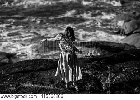Dance woman is engaged in choreography on the Atlantic coast. Black and white photo.