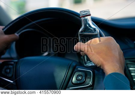 Closeup Of Drunk Man Hands On The Steering Wheel With A Bottle Of Vodka. Driving Under Alcohol Influ