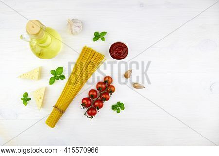 Ingredients For Making Pasta: Linguini, Tomato, Sauce, Basil, Cheese On A White Wooden Background. T