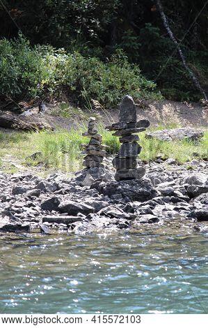 Cairn Stacks Built Along A Lake Shore In Summer