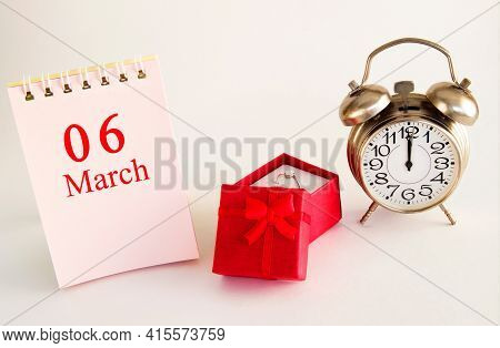Calendar Date On Light Background With Red Gift Box With Ring And Alarm Clock With Copy Space.  Marc