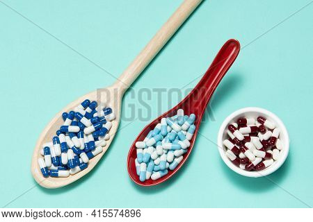 Pharmaceutical Medicine Pill Capsules, In Plastic Spoon On Colorful Background.