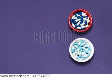 Pharmaceutical Medicine Pill Capsules, In Plastic Bowl On Colorful Dark Background.