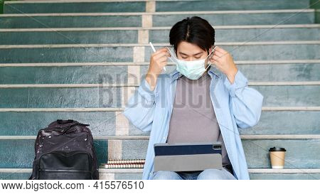 Young Asian Campus Student Man Wearing Protection Mask While Sitting In Campus, Coronavirus Preventi