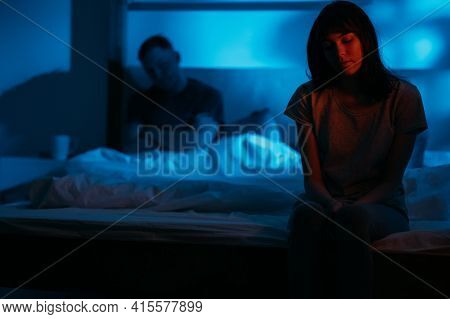 Unhappy Couple. Domestic Violence. Female Abuse. Scared Insecure Humiliated Woman Sitting On Bed On