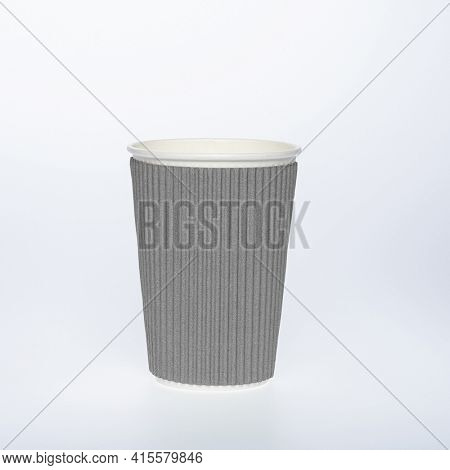 Photo of a disposable gray paper cup on a white background. Photo of a colored coffee cup made of recyclable materials. Empty paper coffee cup.