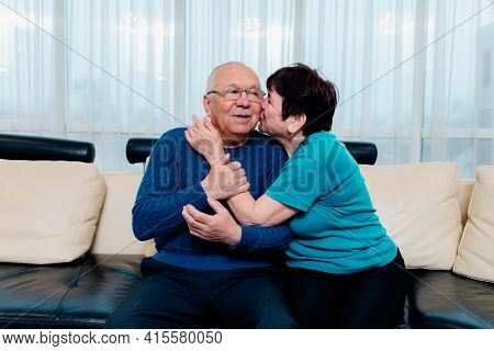 Loving Older Wife Kissing Smiling Husband On Cheek, Expressing Love And Care, Aged Senior Couple Enj