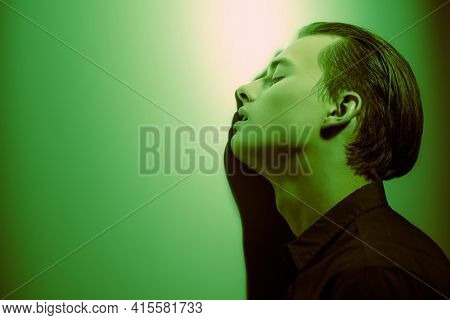Handsome young man stands, sad and alone, leaning against the wall in dark green lighting. Feelings and emotions.