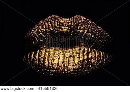Golden Lips Closeup On Balck. Gold Metal Lip. Beautiful Makeup. Golden Lip Gloss On Beauty Female Mo