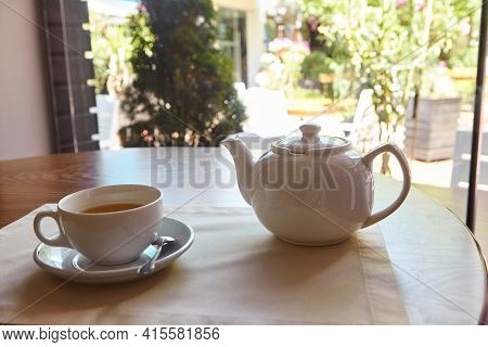 The Table Is Set For Tea. A Teapot And A Tea Cup Are Placed On The Table Overlooking The Terrace