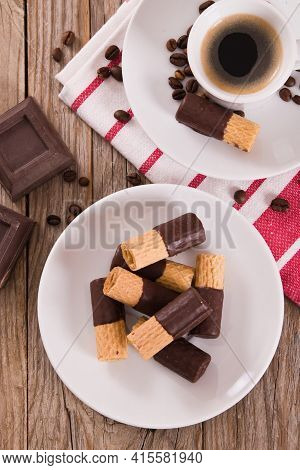 Chocolate Wafer Rolls With Coffee On White Dish.