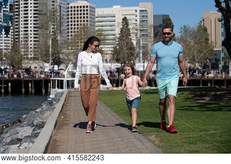 Happy Family Concept. Parents With Son Walking In The City. Family Taking A Walk On Street. Young Co