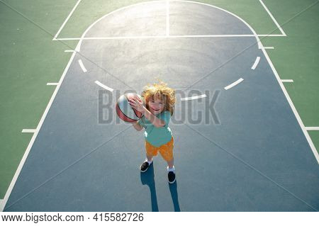 Cute Smiling Boy Plays Basketball. Kid Shooting Basketball Ball And Playing Basketball. Healthy Chil
