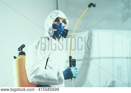 Decontamination Services Worker Wearing Personal Protective Equipment, Spraying Disinfectant.