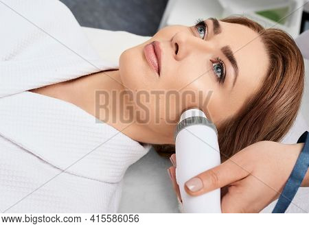 Beautician Using An Acoustic Wave Machine Rejuvenates The Skin Of A Womans Face. Painless Skin Rejuv