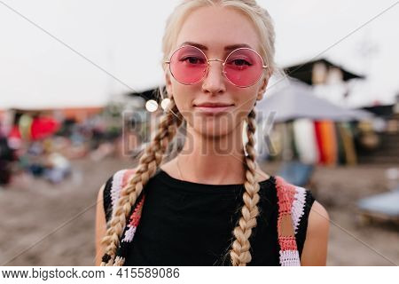Close-up Portrait Of Pleased Fair-haired Woman Wears Round Pink Sunglasses. Outdoor Shot Of Good-loo