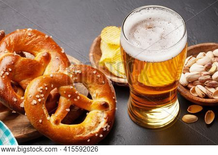 Lager beer mug, nuts, potato chips and fresh baked homemade pretzel with sea salt on stone table. Classic beer snack