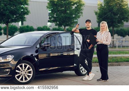 Young Blond Woman Consultant Shows The Customer The Car Outdoors. A Man Buys A Car. Happy Buyer Hold