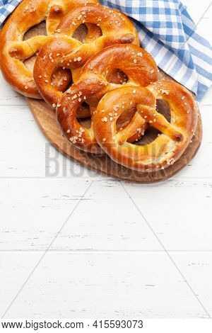 Fresh baked homemade pretzel with sea salt on wooden table. Classic beer snack. Top view flat lay with copy space