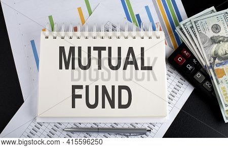 Mutual Fund Text Written On The Notebook With Chart,calculator And Dollars