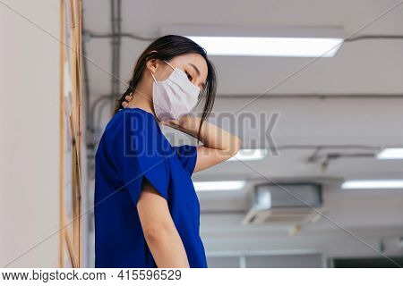 Tired And Frustrated Young Asian Female Doctor Wearing Uniform And Surgical Mask Suffering From Neck