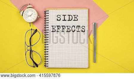 Side Effects Notice On Notepad With Pen, Glasses And Alarm Clock