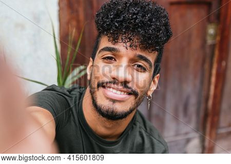 Self-portrait Of Young Attractive Latino Man With His Mobile Phone. He Wears A Dark Green T-shirt An