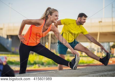 Young Couple Is Exercising Outdoor. They Are And Stretching And Warming Up For Jogging.