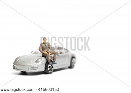 Miniature People Business Man Sitting On A Car