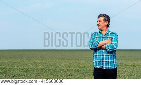 Experienced And Confident Farmer Stands On His Field. Portrait Of Senior Farmer Agronomist In Wheat