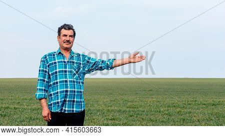 Experienced And Confident Farmer Stands On His Field With Hand Outstretched. Portrait Of Senior Farm