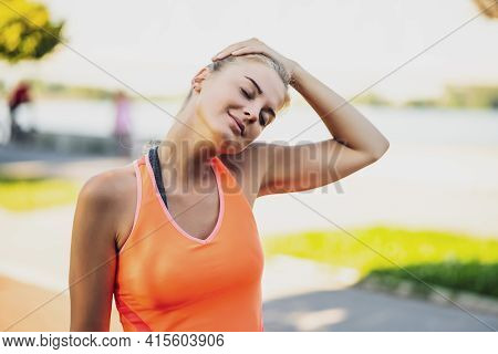 Young Woman Is Exercising Outdoor. She Is Stretching Her Body And Warming Up For Jogging.